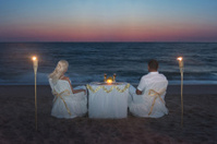 Couple at sea beach during luxury romantic dinner with candles