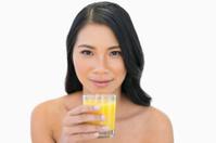 Sensual nude model holding orange juice