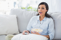 Astonished woman relaxing on the sofa eating popcorn
