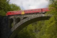 Red train crossing stone bridge
