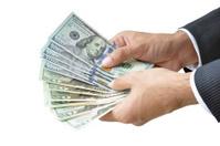 Hands holding money - United States Dollar (USD) bills
