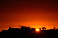 Sun rising behind a Saskatchewan farmyard