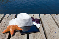 Tablet PC and straw hat at the swimming lake