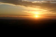 Sun Rising through Distant Clouds
