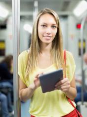Female using ereader in subway