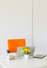 Modern creative workspace with computer and orange chair