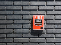 fire alarm on the black brick wall