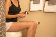 woman sitting on toilet with pregnancy test