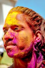 Happy indian man celebrating holi