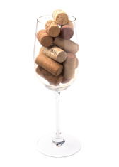 Wine glass filled with wine corks