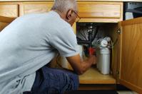 Man making under sink repairs