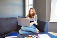 Girl on sofa using laptop studying