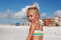 Little girl on beach with houses in backrgound