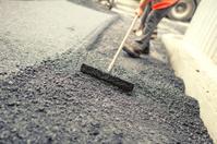 Worker levelling fresh asphalt on a road construction site