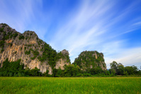 Mountain with green rice field and blue sky in Phitsanulok