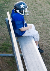 Lone benched youth football player.