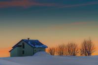 Alpine hut in winter sunset
