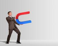 Businessman in suit holding big magnet