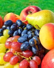 Ripe grape, peaches, pears on the grass
