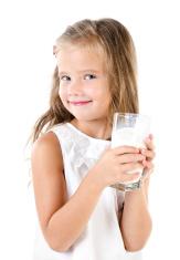 Smiling little girl drinking milk isolated