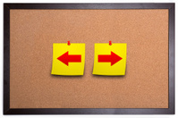Arrows sign on corkboard with adhesive note