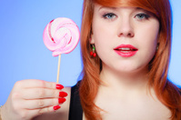 Sexy young woman holding candy. Redhair girl eating sweet lollip