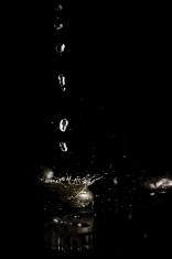 Water droplets splashing onto a black surface