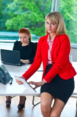 business woman working on tablet with colleague in background
