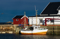 Boat at dock in the harbor of Henningsfaer, Norway
