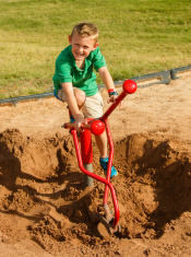 Boy working construction with digger in dirt pile.