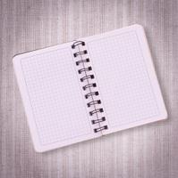 Pure notebook for recording menu, recipe on tablecloth tartan.