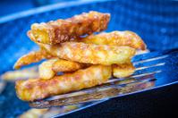 Potato chips frying in oil in a pan