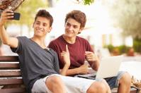 Two Teenage Boys Sitting On Bench Taking Selfie In Park