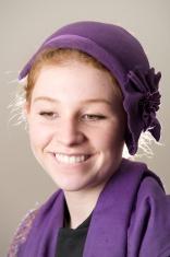 Smiling redhead in purple hat biting lip