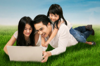 Family using laptop on the meadow