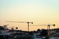 Construction cranes at sunset.