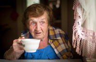 Old woman drinking tea at the window in his house.