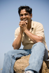 Happy Indian Male sitting on a rock and smiling