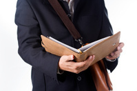 business man with briefcase and reading the book