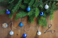 Silver thread, scissors, xmas tree and balls on wooden backgroun