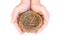 Hands protecting an empty bird's nest