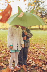 little girl and boy hiding under an umbrella