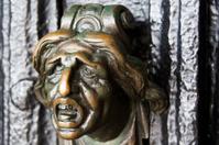 Old skulptured brass knob at a black door in Venice