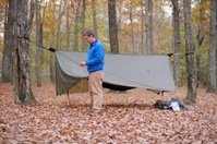 Man putting tarp over camping hammock