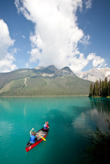 Woman and Young Boy Canoeing on Beautiful Mountain Lake