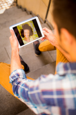 Man Looks At Photo Of Girlfriend On Tablet