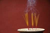 Sticks of burning incense on dark red background
