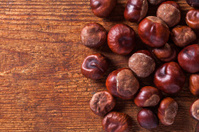 Some chestnuts on wooden background.