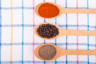 Whole and ground pepper in a wooden spoon .