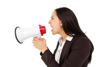 Pretty businesswoman shouting with megaphone